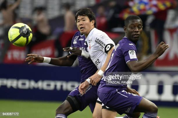 Toulouse's Ivory Coast forward Max Gardel vies with Dijon's SouthKorean midfielder Chang Hoon Kwon during the French L1 football match between...