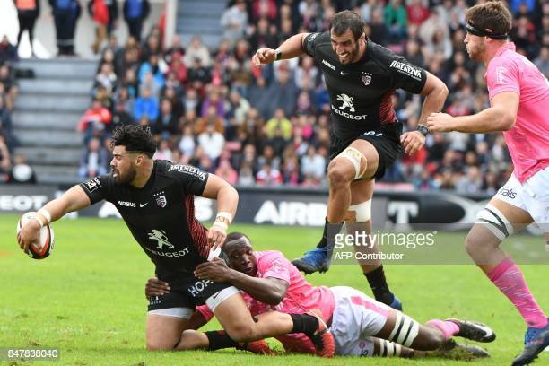 Toulouse's New Zealand centre Jarrod Poi collapses with Stade Francais French number eight Segou Macalou during the French Top 14 rugby union match...