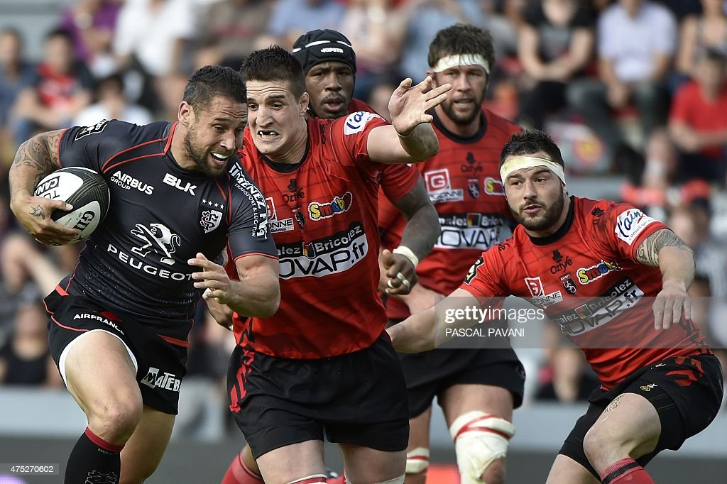 Toulouse's New Zeland fly-half Luke Mc Alister (L) runs with the ball during the French Top 14 rugby union match between Toulouse and Oyonnax on May 30, 2015 at the Ernest Wallon Stadium in Toulouse, southern France.