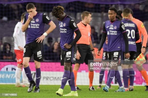 Toulouse's players react after losing the French L1 football match between Toulouse Football Club and Stade de Reims at the Municipal Stadium in...