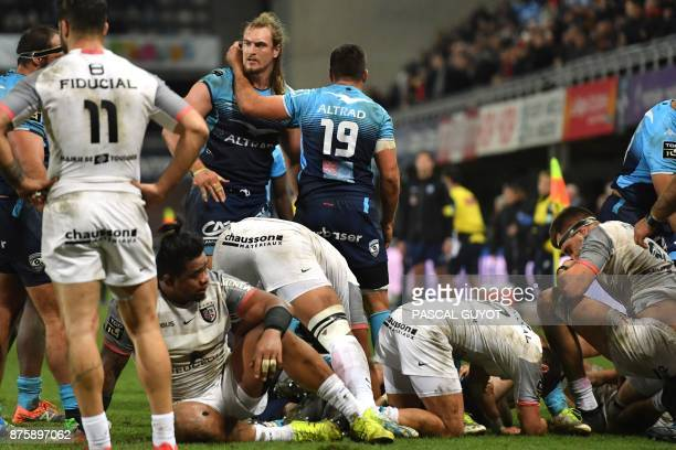 Toulouse's players react on the ground next to Montpellier's South African lock Jacques Du Plessis after being defeated by Montpellier during their...