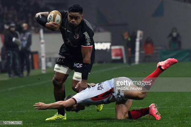 Toulouse's Samoan lock Iosefa Tekori is tackled by Toulon's French fly-half Louis Carbonel during the French Top 14 rugby union match between...