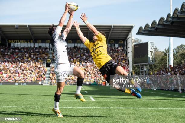 TOPSHOT Toulouse's South African flyhalf Tristan Tedder and La Rochelle's French wing Arthur Retiere jump for the ball during the French Top 14 rugby...