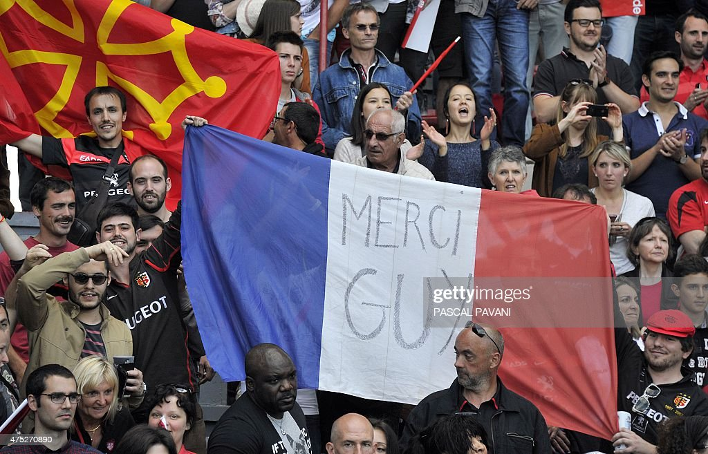 Toulouse's supporters wave a French flag with 'Thank you Guy ' written on it at the end of the French Top 14 rugby union match between Toulouse and Oyonnax on May 30, 2015 at the Ernest Wallon Stadium in Toulouse, southern France.