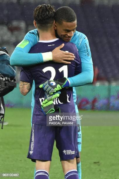 Toulouse's Swedish midfielder Jimmy Durmaz and Toulouse's French goalkeeper Alban Lafont celebrate their 10 victory and their staying in League 1 at...