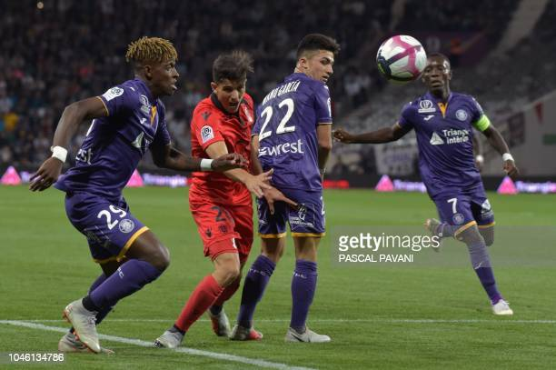 Toulouse's Swiss defender Jacques François Moubandje and Nice's Algerian defender Youcef Atal vies for the ball during the French L1 football match...