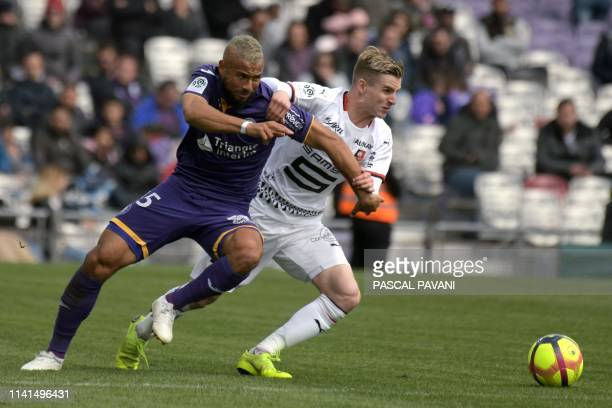 Toulouse's Trinidad midfielder John Bostock vies with Rennes French midfielder Benjamin Bourigeaud during the French L1 football match between...