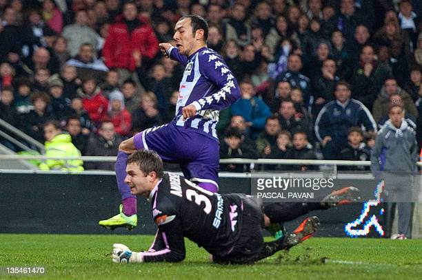 Toulouse's Turkish forward Umut Bulut scores in spite of Evian goalkeeper Danish Stephan Andersen's defense during the French L1 football match...
