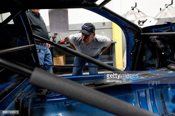 A tour attendee views the interior of a General Motors Co Chevrolet COPO Camaro chassis inside the company's build center in Oxford Michigan US on...