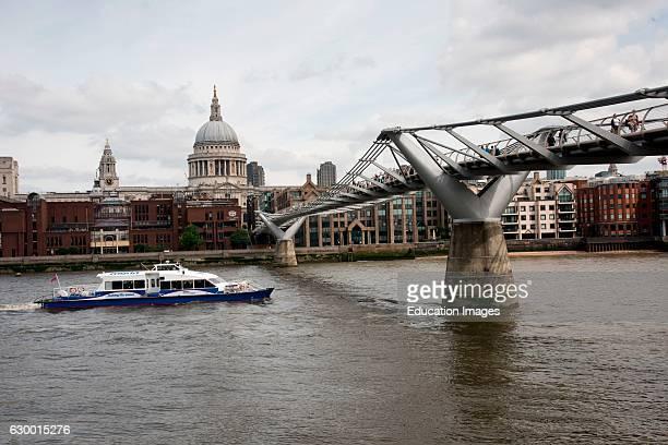Tour boat cruises under Millennium Bridge and past St Paul's cathedral London England