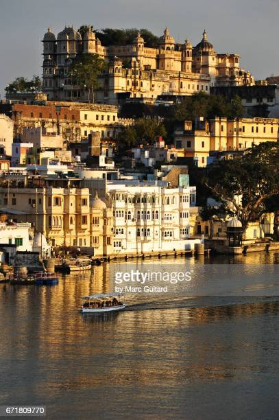 a tour boat drifts beneath the imposing city palace of udaipur at sunset, rajasthan, india - udaipur stock pictures, royalty-free photos & images