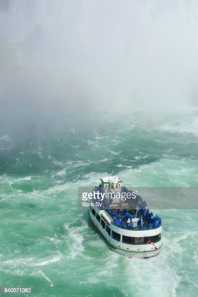 a tour boat heading into the mist created by niagara falls, ontario, canada - ferry stock pictures, royalty-free photos & images