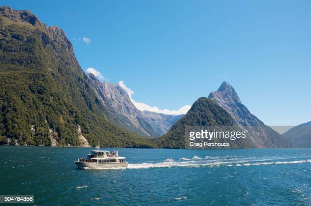 Tour boat in Milford Sound before Mitre Peak and surrounding mountains.