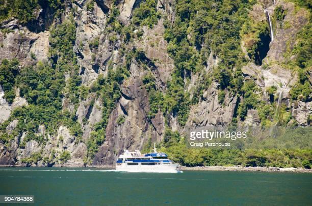 Tour boat in Milford Sound below sheer cliffs.