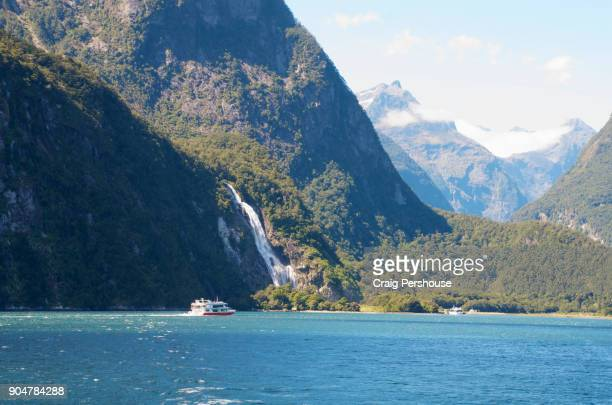 Tour boat in Milford Sound below waterfall.