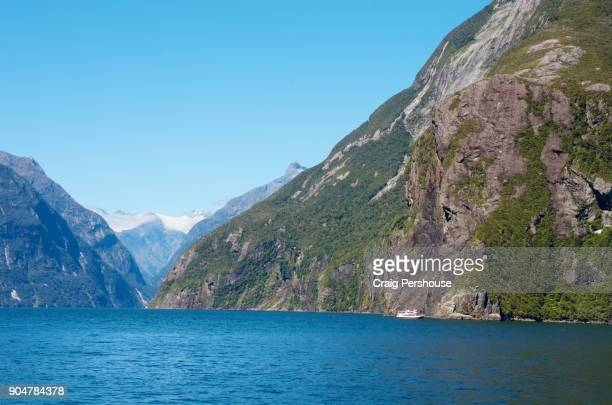 A tour boat in Milford Sound is dwarfed by a nearby cliff and mountain.