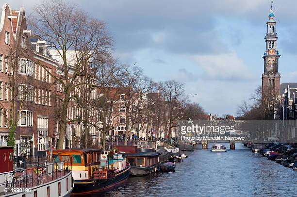 Tour Boat on Canal with Westkerk Spire in Amsterdam in Winter