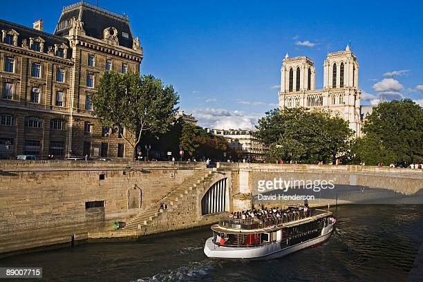 Tour boat on the River Seine by Ile de la Cite and Notre Dame cathedral, Paris, France