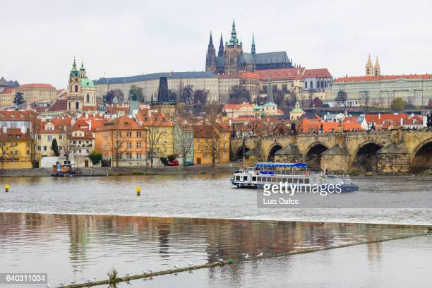 Tour boat on the Vltava river next to Charles Bridge on a Auntumn day. Prague