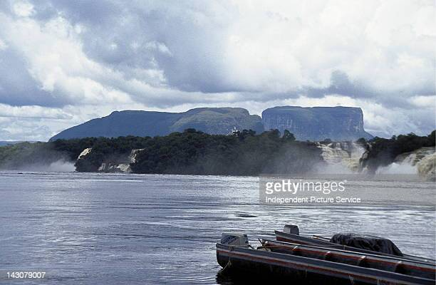 Tour boats on the Carrao River at Hacha Falls with mesas called tepuis in the background, Venezuela.