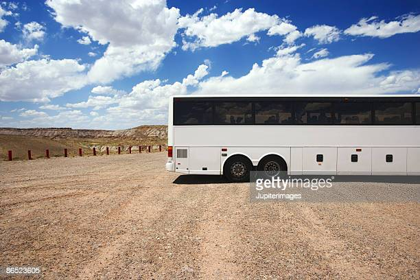 Tour bus parked in dirt lot