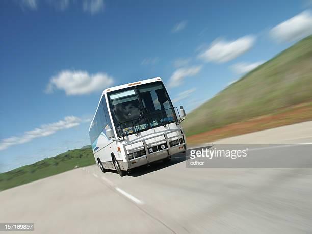 Tour bus speeding down empty highway