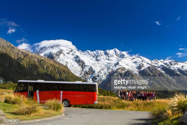 A tour bus stops in front of Mount Cook.