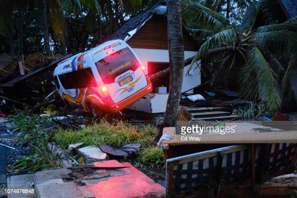 A tour bus with its lights still running sits on a bungalow wrecked by a tsunami at a resort hotel on December 23 2018 in Tanjung Lesung Indonesia...