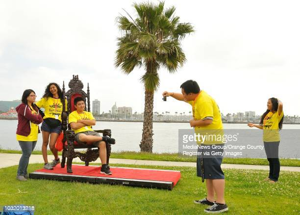 BEACH CALIF USA Tour de Cure volunteer David Ly takes a picture of fellow volunteer Peter Cheng as his sits in a thrown near the ending of the ride...