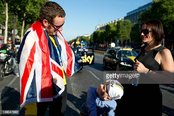 Tour de France 2012 winner Yellow jersey British Bradley Wiggins wrapped in a national flag looks at his son as his wife Catherine looks on during a...