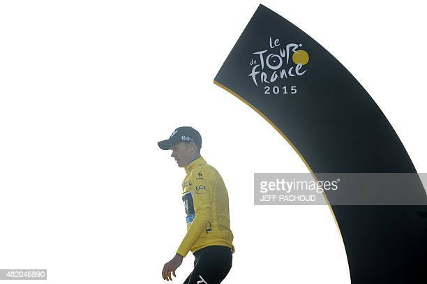 Tour de France 2015's winner Great Britain's Christopher Froome walks wearing his overall leader's yellow jersey during the podium ceremony on the...