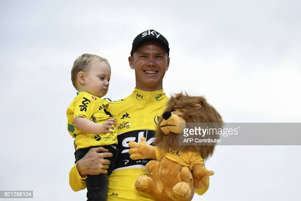 TOPSHOT Tour de France 2017's winner Great Britain's Christopher Froome celebrates his overall leader yellow jersey with his child Kellan on the...