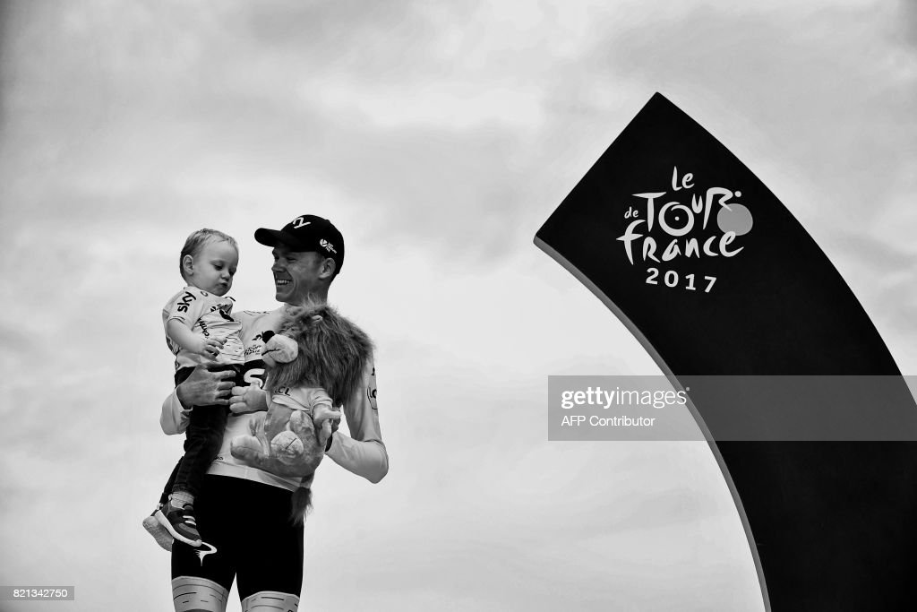 Tour de France 2017's winner Great Britain's Christopher Froome celebrates his overall leader yellow jersey with his child Kellan on the podium at the end of the 103 km twenty-first and last stage of the 104th edition of the Tour de France cycling race on July 23, 2017 between Montgeron and Paris Champs-Elysees. /