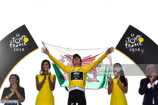 Tour de France 2018 winner Great Britain's Geraint Thomas holds a Welsh flag as he celebrates his overall leader yellow jersey on the podium after...