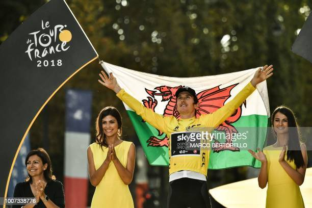 TOPSHOT Tour de France 2018 winner Great Britain's Geraint Thomas holds the Welsh flag as he celebrates his overall leader yellow jersey on the...