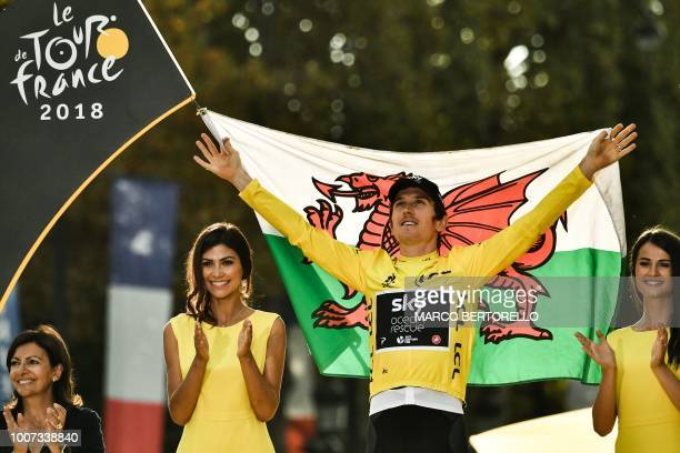 Tour de France 2018 winner Great Britain's Geraint Thomas holds the Welsh flag as he celebrates his overall leader yellow jersey on the podium...