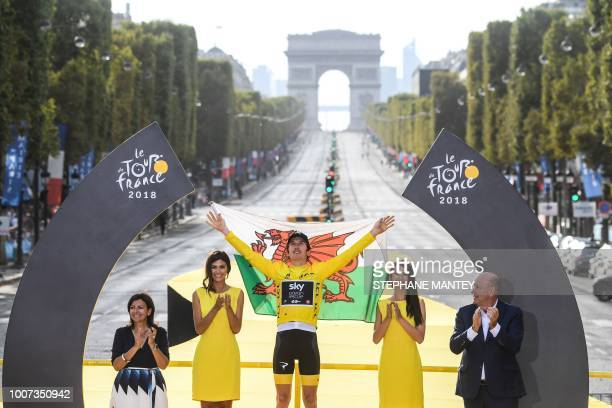Tour de France 2018 winner Great Britain's Geraint Thomas wearing the overall leader's yellow jersey holds a Welsh flag flanked by Paris Mayor Anne...