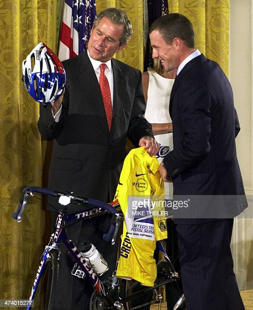 Tour de France victor Lance Armstrong of the US presents US President George W Bush with a US Postal Service yellow jersey and a replica of the bike...