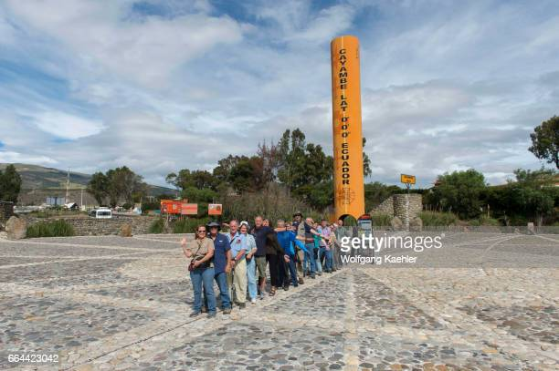 A tour group is standing with one foot in the northern hemisphere and the other foot in the southern hemisphere at the Quitsato equator monument and...