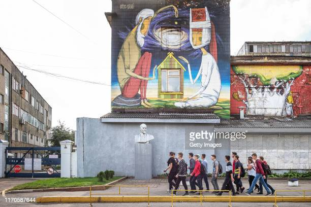 A tour group walking past a statue of Lenin and a recently painted stateapproved graffiti on September 17 2019 in Minsk Belarus Recent months have...