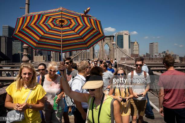 A tour group walks across the Brooklyn Bridge on August 20 2019 in New York City NYC Company the city's tourism marketing agency reports that New...