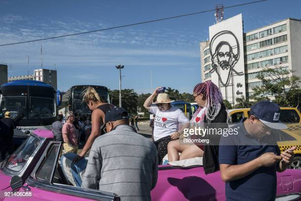 A tour guide assists people getting into a vintage American car at Revolution Square in Havana Cuba on Tuesday Jan 30 2018 The latest statistics from...