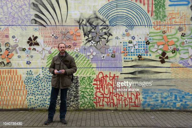 Tour guide Bert de Bisschop stands in front of a colorful wall in the district of Molenbeek in Brussels Belgium 28 January 2016 He regularly guides...