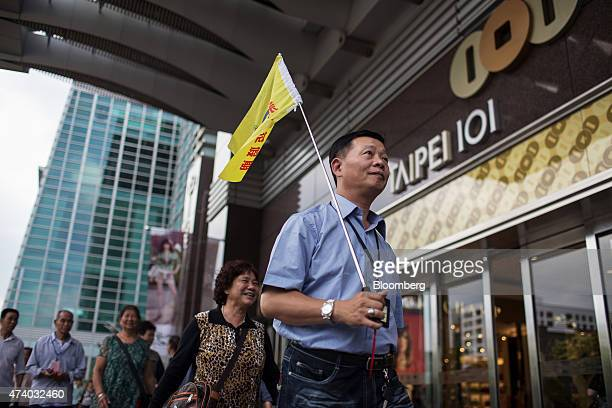 A tour guide center carrying a flag walks past the entrance to the Taipei 101 building in Taipei Taiwan on Saturday May 16 2015 Taiwan is scheduled...