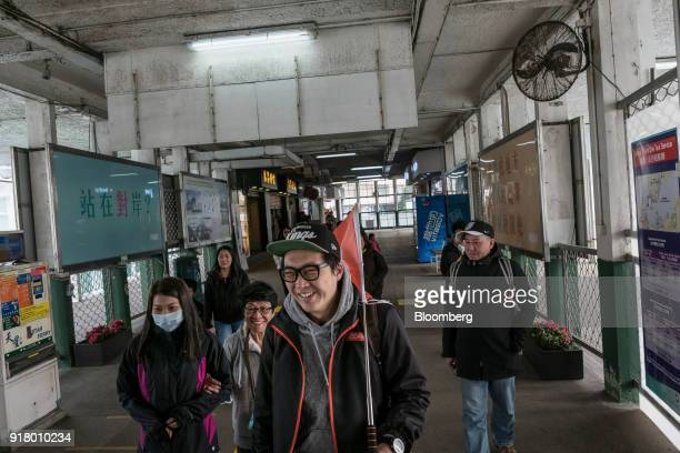 A tour guide center holds a flag while leading a group of tourists during a guided walking tour hosted by Klook Travel Technology Ltd in Hong Kong...