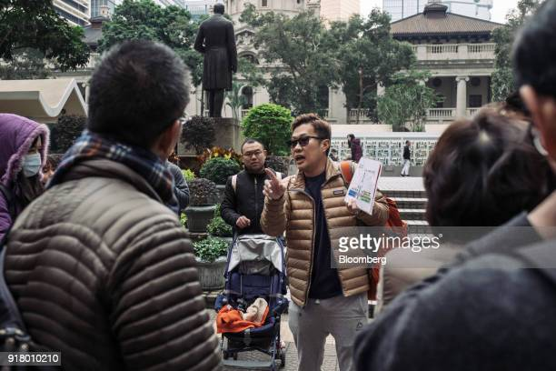 A tour guide center holds a map while speaking to a group of tourists during a guided walking tour hosted by Klook Travel Technology Ltd in Hong Kong...