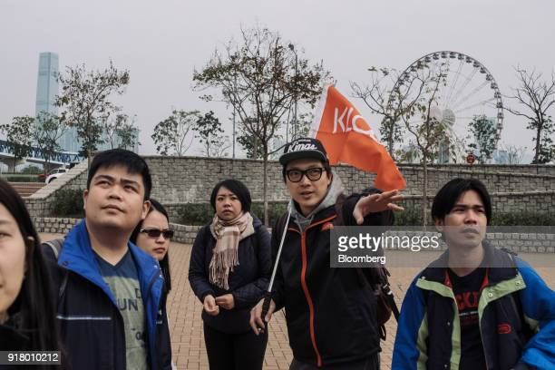 A tour guide center right holds a flag while introducing a location to a group of tourists during a guided walking tour hosted by Klook Travel...
