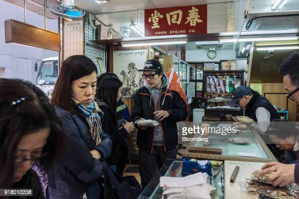 A tour guide center speaks to a group of tourists at a traditional Chinese medicine pharmacy during a guided walking tour hosted by Klook Travel...
