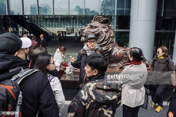 A tour guide center speaks to a group of tourists in front of a statue of a lion at the HSBC Holdings Plc headquarters during a guided walking tour...
