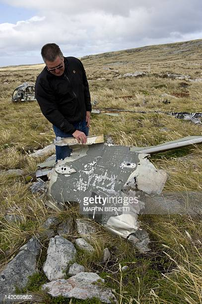 Tour guide Derek Pettersson shows part of the wreckage of an Argentine helicopter used during the 1982 conflict near Port Stanley in the Falkland...